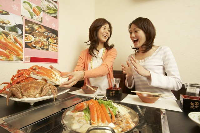 Japanerinnen beim Krabbenessen am Tisch