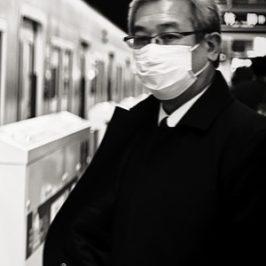 Mann mit weißer Mund-Maske in Japan in U-Bahnhof